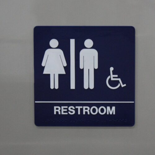 Placard denotes wheelchair accessible restroom entrance.