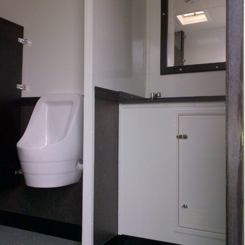 Privacy is ensured by dividing walls that separate the urinals from the sink area.