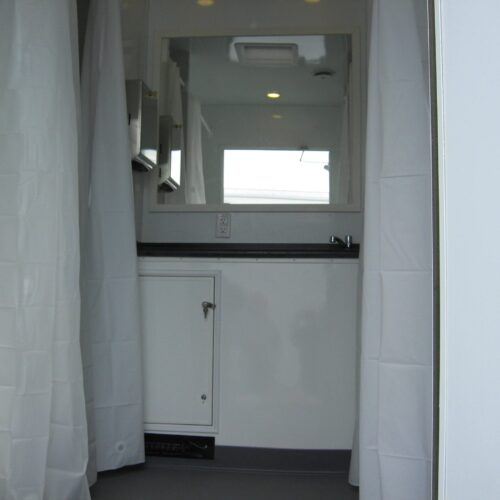 4 showers line the walls, framing a large countertop and sink with running water.