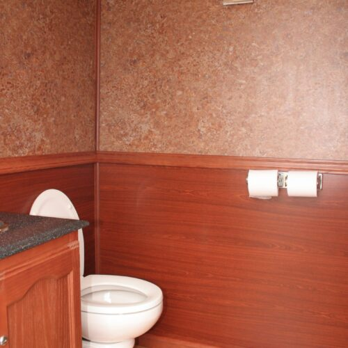 Comfortable toilet area with wood tone walls