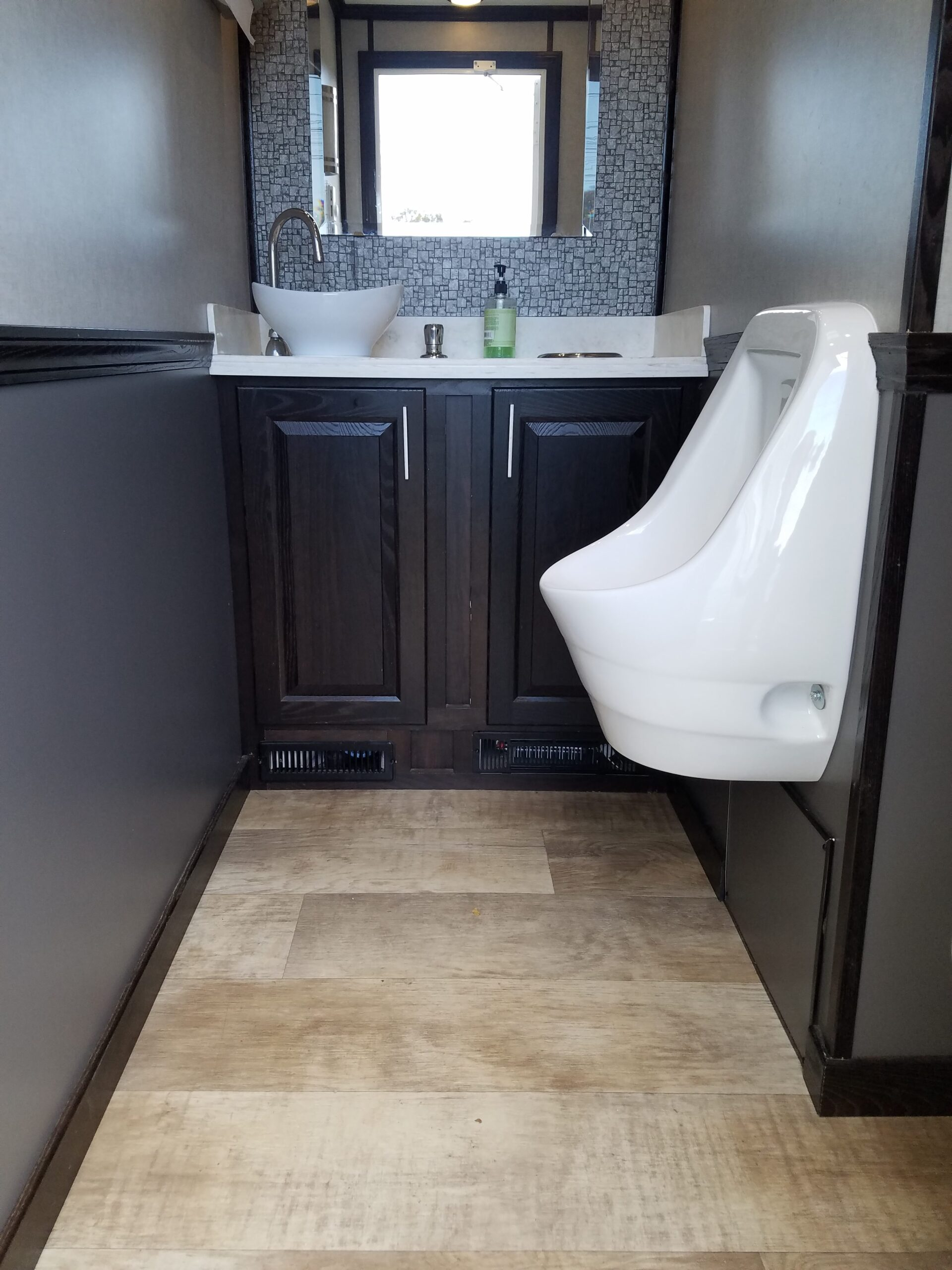 Zoomed out inside view of male restroom station with a mirror, a urinal and a sink