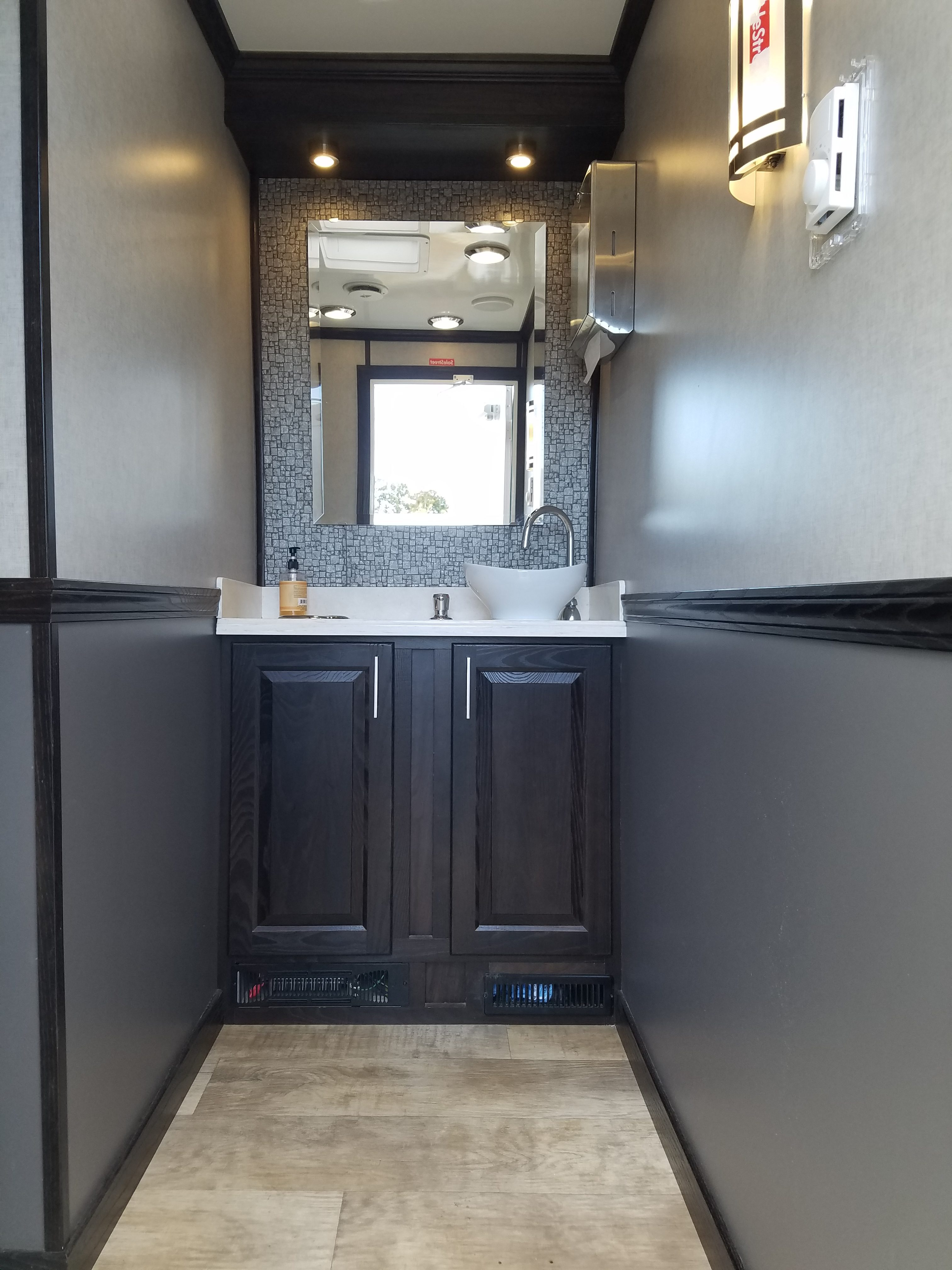 Zoomed out inside view of restroom station with a mirror and sink