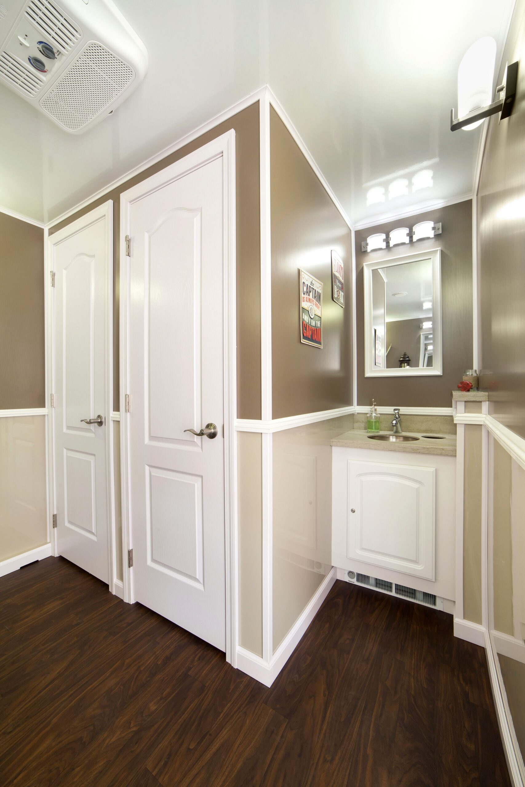 Restroom interior with two closed doors and a sink with mirror