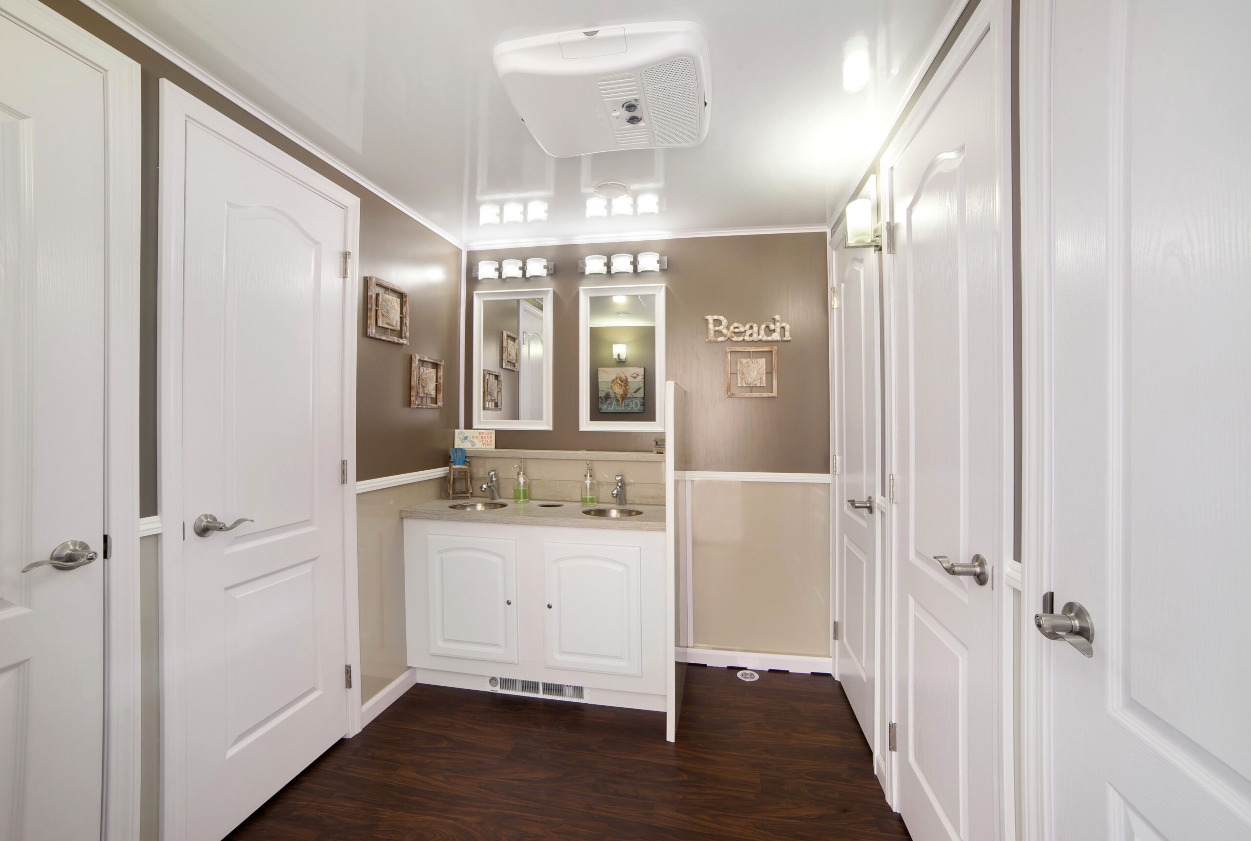 Inside view of a five station restroom trailer with two sinks and a wooden floor