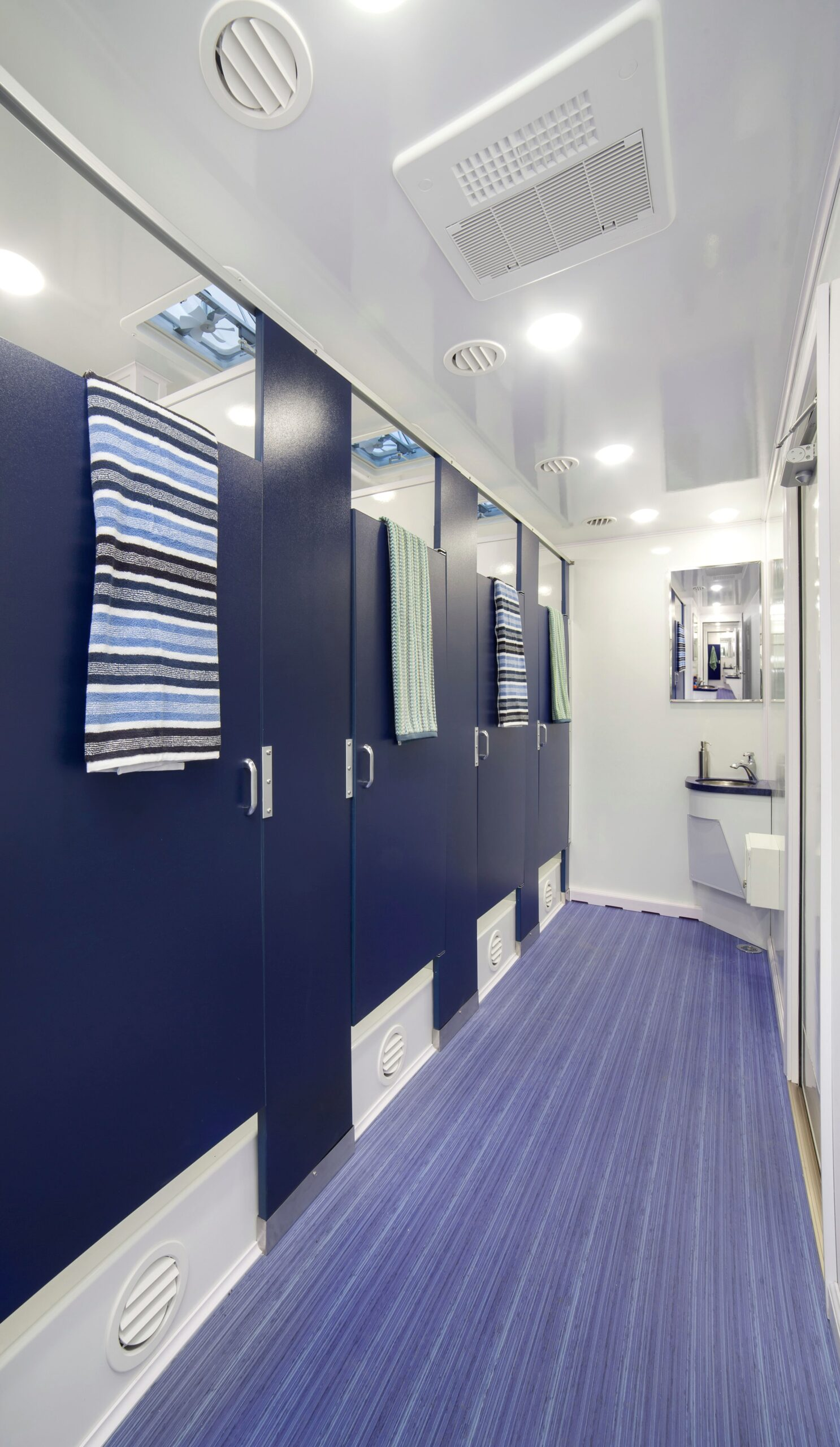 Interior of shower restroom with blue doors and sink at the end of a passage