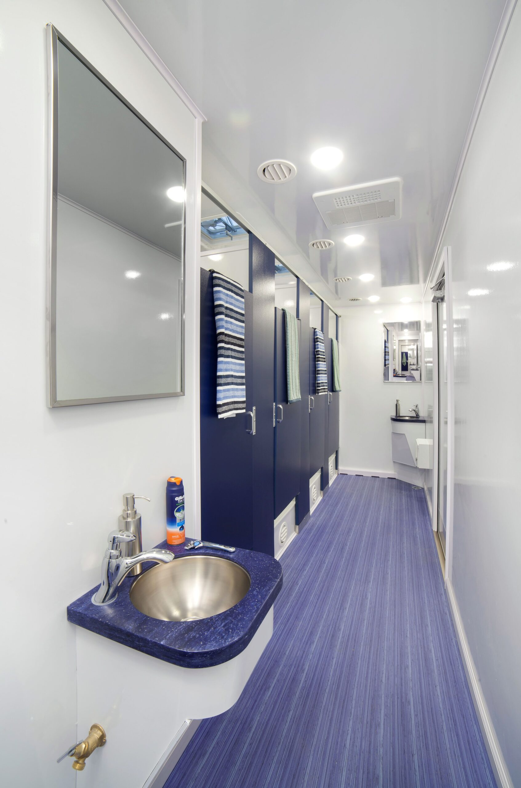 Inside of a shower restroom trailer with a sink and four blue doors to shower booths