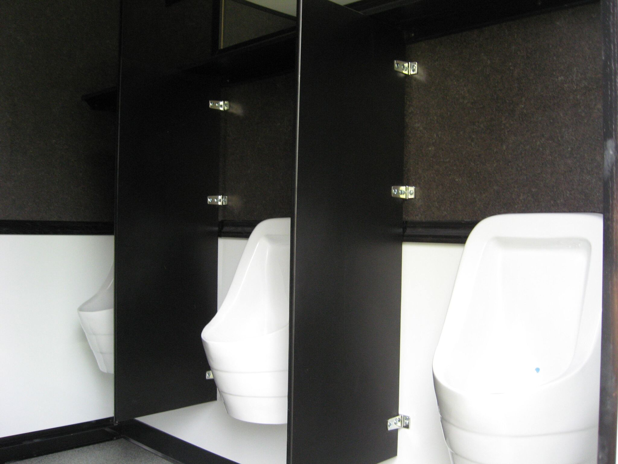 Three urinals installed in a restroom trailer and separated by separators