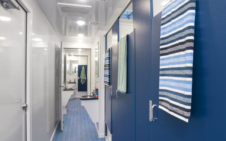 A zoomed in inside view of restroom stations with blue doors and colorful towels