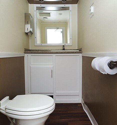 Zoomed out full inside view of restroom station with a stall, a mirror, tissue holder and a sink